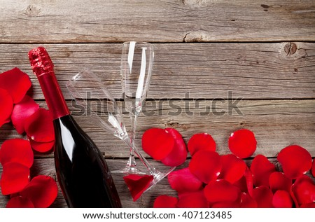 Champagne and rose petals over wooden background - stock photo