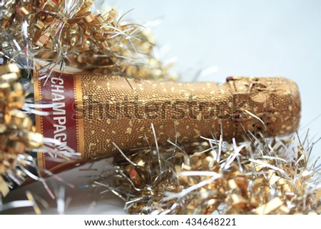 Champagne bottle and christmas decorations in gold - stock photo