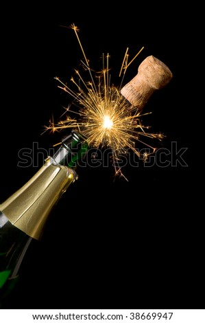 Champagne bottle and cork with lit firework - stock photo