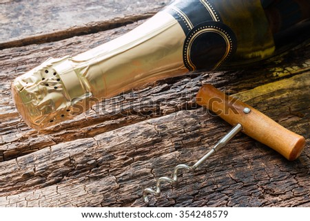 champagne bottle and corkscrew - stock photo