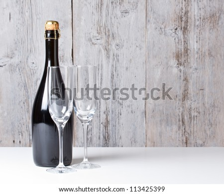 Champagne bottle and glasses on table - stock photo