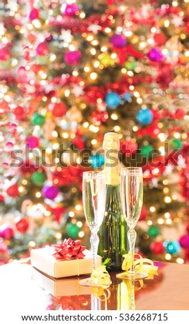 Champagne bottle and glasses with gift box on Mahoney table for holiday celebration.