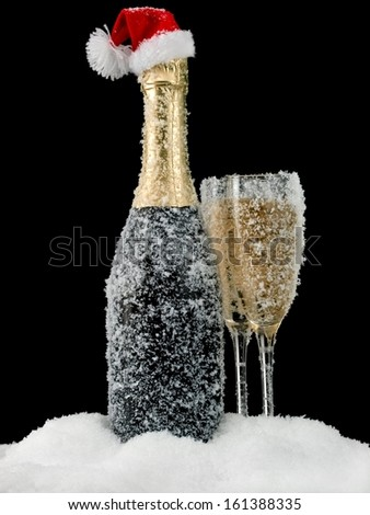 Champagne bottle and two glasses, covered with snowflakes - stock photo