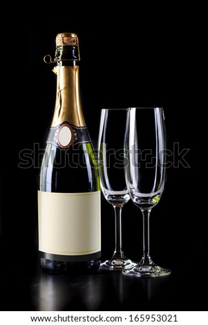 champagne bottle and two glasses on black background - stock photo
