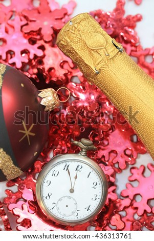 Champagne bottle, christmas ball and a vintage pocket watch - stock photo