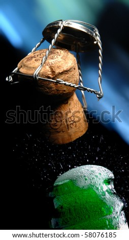 Champagne bottle cork popping,  on black -  blue background, closeup - stock photo