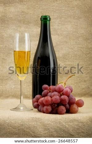 Champagne bottle, goblet, grapes on sacking - stock photo