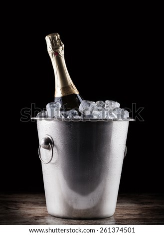 Champagne bottle in a bucket with ice on the dark background - stock photo
