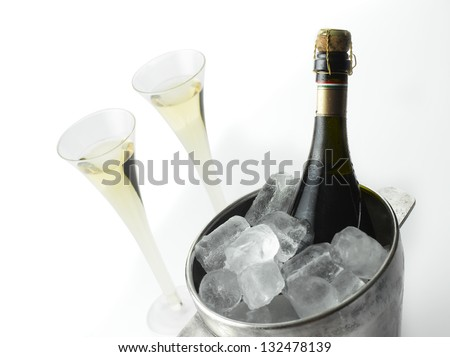 Champagne bottle in an ice bucket, two champagne flutes. Isolated on white. - stock photo