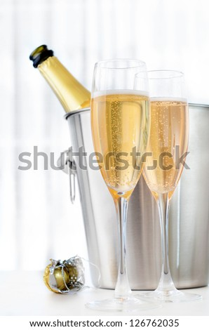 Champagne bottle in bucket with glasses of champagne - stock photo