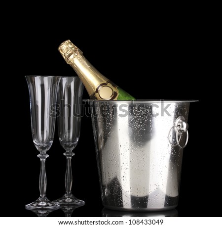 Champagne bottle in bucket with ice and glasses isolated on black - stock photo
