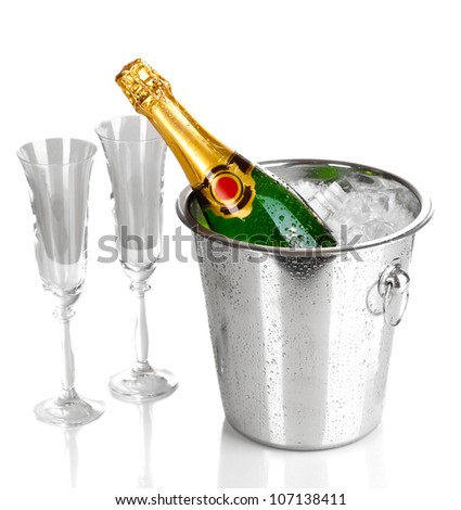 Champagne bottle in bucket with ice and glasses isolated on white