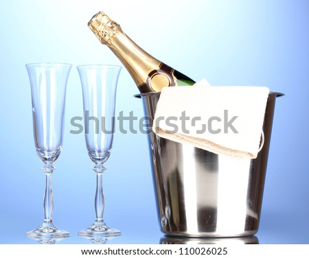 Champagne bottle in bucket with ice and glasses on blue background - stock photo
