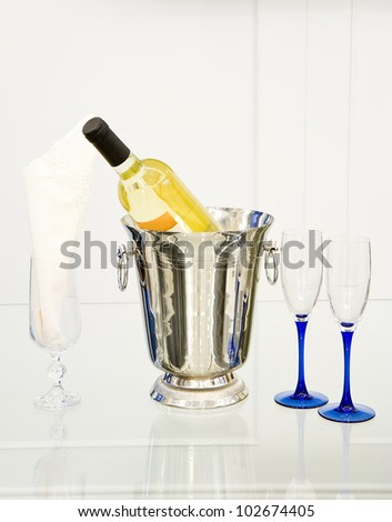 Champagne bottle in cooler and two champagne glasses - stock photo