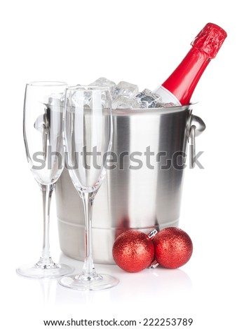 Champagne bottle in ice bucket, two empty glasses and christmas decor. Isolated on white background