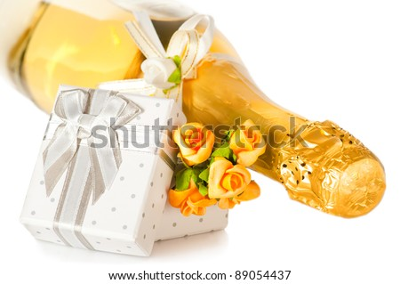 Champagne bottle, present box with bow and flower boutonniere on white background - stock photo