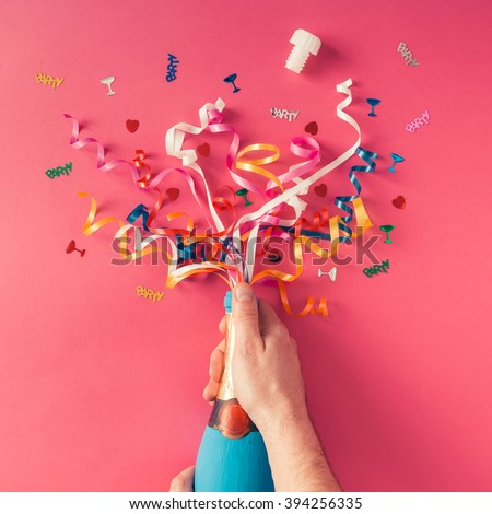 Champagne bottle with colorful party streamers on pink background. Flat lay - stock photo