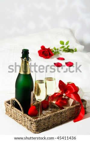 Champagne breakfast in bed with single red rose on pillow and gift wrapped in red ribbon - stock photo