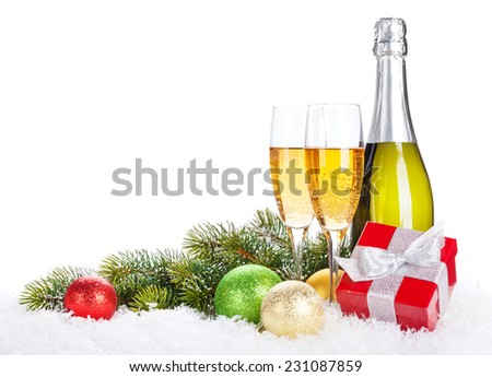 Champagne, christmas decor and gift box over snow and fir tree with copy space - stock photo