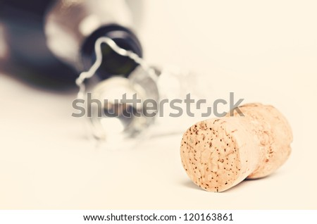Champagne cork against bottle. Toned image - stock photo