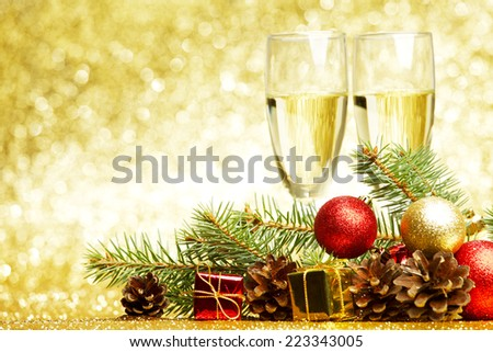 Champagne, fir tree, christmas decor and gifts on golden background - stock photo
