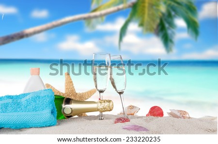 Champagne flutes on sunny beach, celebration theme. - stock photo