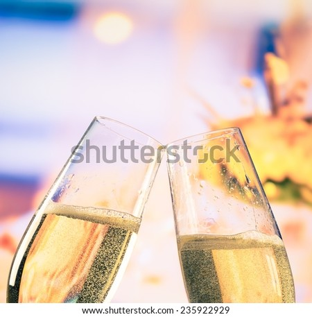 champagne flutes with golden bubbles make cheers on flowers background wedding and valentine day concept - stock photo