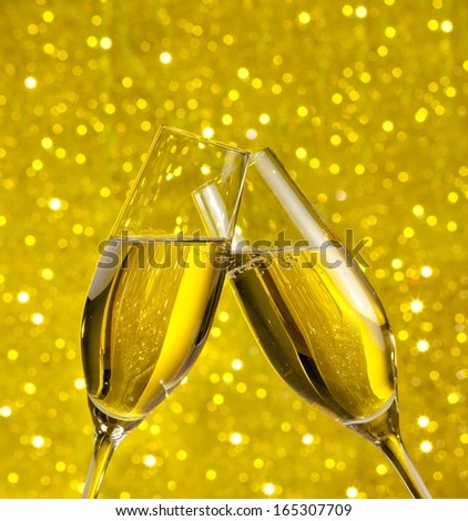 champagne flutes with golden bubbles make cheers on golden light bokeh background