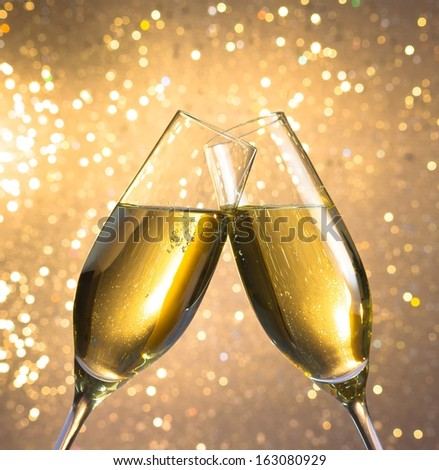 champagne flutes with golden bubbles make cheers on light bokeh background