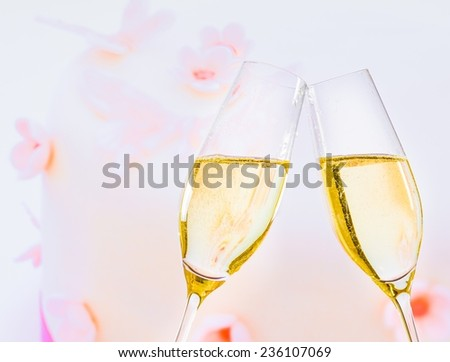 champagne flutes with golden bubbles make cheers on wedding cake background - stock photo