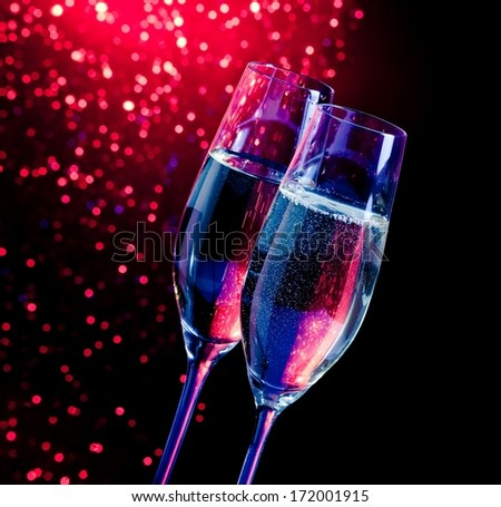 champagne flutes with golden bubbles on dark blue and violet light bokeh background with space for text - stock photo