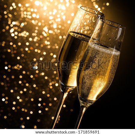 champagne flutes with golden bubbles on dark golden light bokeh background with space for text - stock photo