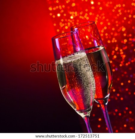 champagne flutes with golden bubbles on dark red and violet light bokeh background with space for text - stock photo