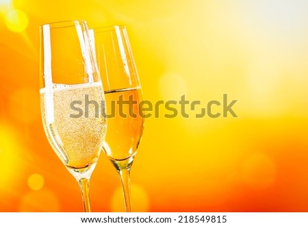 champagne flutes with golden bubbles on golden light background with space for text - stock photo