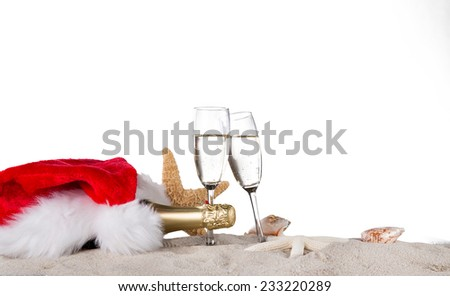 Champagne flutes with santa cap on sunny beach, celebration theme. - stock photo