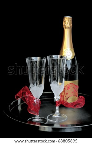 """Champagne for two: Two champagne glasses decorated with """"hearts"""" ribbons on metal tray with bottle of Champagne. Shot on black background. Brand name & logos removed. - stock photo"""