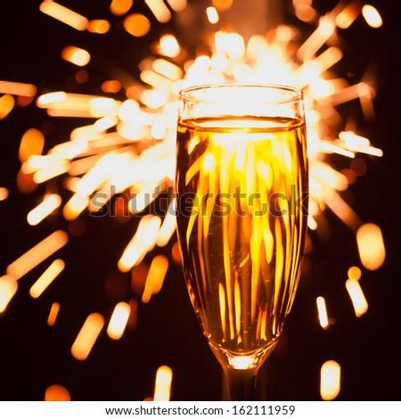 champagne glass against christmas sparkler background - stock photo