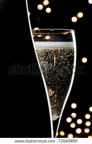 champagne glass and bottle on black background - stock photo