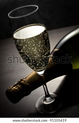 Champagne glass and bottle on the table - stock photo