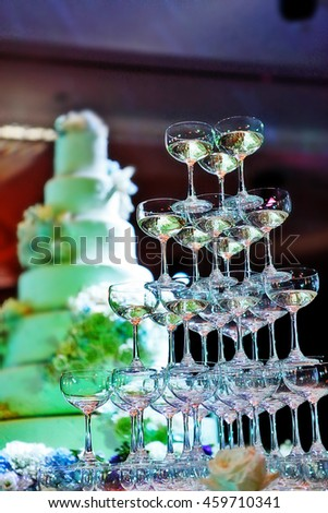 Champagne glass tower and wedding cake in wedding ceremony - stock photo