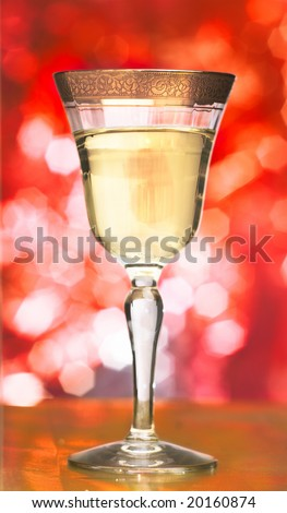 Champagne glass with golden engraved stripe on the top over a red sparkling background - stock photo
