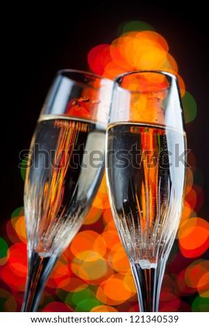 champagne glasses against christmas tree bokeh lights - stock photo
