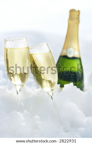 Champagne glasses and bottle in the snow - stock photo