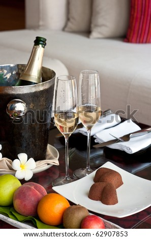 champagne glasses and bottle on the table with fruit and chocolate cake - stock photo
