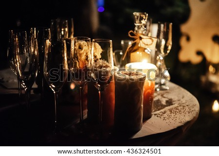 champagne glasses and candle in glass jar on table at evening wedding ceremony - stock photo