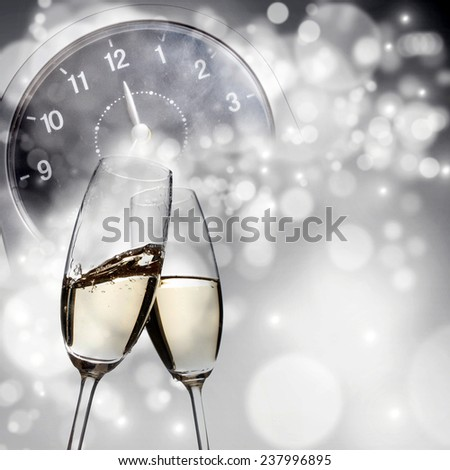 Champagne glasses and clock at midnight - stock photo