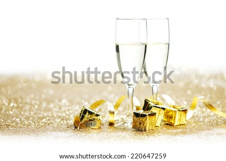 Champagne glasses and gifts on glitters with white copy space - stock photo