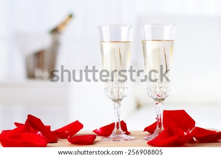 Champagne glasses and rose petals for celebrating Valentines Day - stock photo