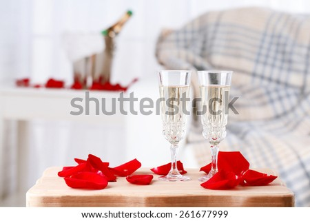 Champagne glasses and rose petals for celebrating Valentines Day