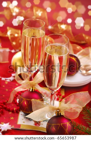 champagne glasses on festive table in red and golden colors - stock photo